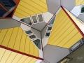 Raam in een Kubus woning. De Kubuswoningen in Rotterdam zijn 38 kubusvormige paalwoningen en 13 bedrijfskubussen bij de Blaak nabij de Oude Haven. Ze zijn gebouwd tussen 1982 en 1984, na een eerste presentatie van de plannen in 1978. Het ontwerp van Piet Blom is een variant op de Helmondse kubuswoning in een iets groter maatraster. Het viaduct op één hoog heet officieel de Overblaak, maar het hele complex staat bekend als het Blaakse Bos. De Kubuswoningen zijn gebouwd in de vorm van een gekantelde kubus op een paal, en worden ook wel paalwoning of boomwoning genoemd. (juli 2018)
