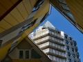 """Doorkijk via de Kubuswoningen naar De Blaaktoren. De Blaaktoren is een woontoren aan de Binnenrotte bij de Blaak in Rotterdam. Aan het opvallende puntvormige dak ontleent het gebouw zijn meer bekende bijnaam """"Het Potlood"""". Het is een van de markantste gebouwen van Rotterdam en vormt met de naastgelegen kubuswoningen een bekend herkenningspunt in de stad. De Blaaktoren is in 1984 opgeleverd. (juli 2018)"""
