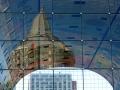 """Spiegeling van de De Blaaktoren. in de Markthal. De Blaaktoren is een woontoren aan de Binnenrotte bij de Blaak in Rotterdam. Aan het opvallende puntvormige dak ontleent het gebouw zijn meer bekende bijnaam """"Het Potlood"""".  (juli 2018)"""